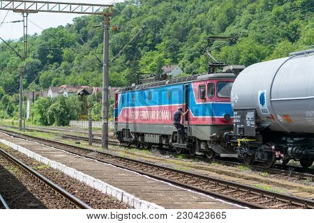 Sighisoara, Romania - 1 July 2016: Train Conductor Get On The Train Locomotive With Cargo Wagons At