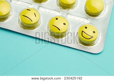 Yellow Pills Andfunny Faces In A Blister On A Blue Background. The Concept Of Antidepressants And He
