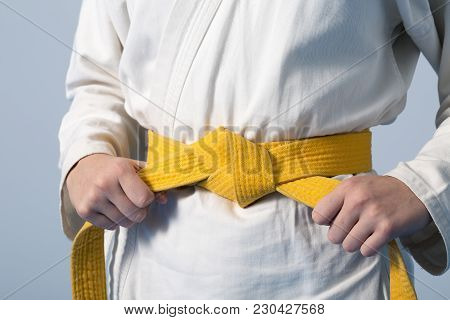 Hands Tightening Yellow Belt On A Teenage Dressed In Kimono For Martial Arts