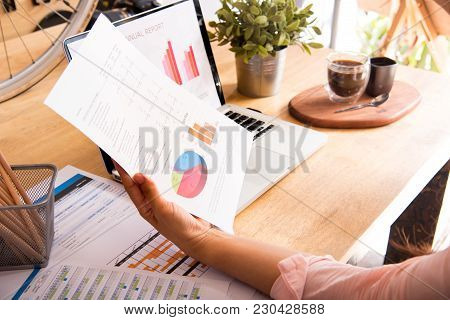 Side View Of Young Audit Woman Using Laptop And Reading Annual Report , Accounting Graph And Documen