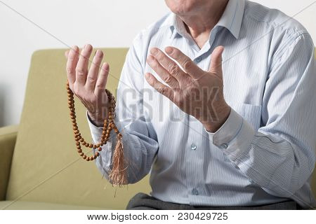 Praying Hands Of An Old Man Holding Rosary Beads. S