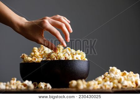 The Hand Reaches For A Bowl With Tasty Popcorn.
