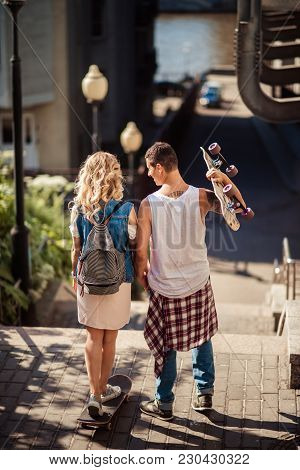 Back View Of Female And Male Teenagers With Skateboard Have Active Activities Outdoor During Summer