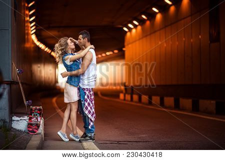 Portrait Of Female And Male Skaters Embrace Passionately, Going To Kiss, Stand Against Tunnel Backgr