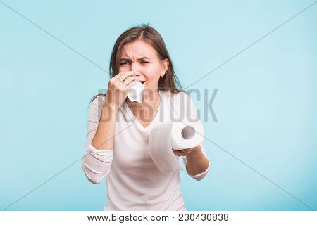 Young Man Has A Runny Nose On Blue Background.