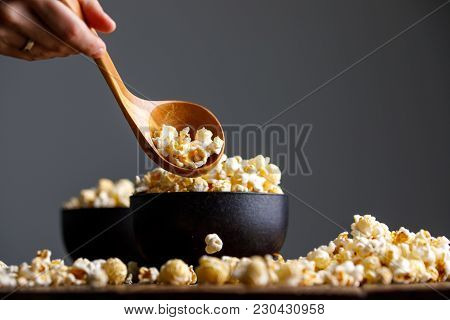 A Ceramic Bowl Full Of Popcorn And A Hand With A Wooden Spoon Scoops It.