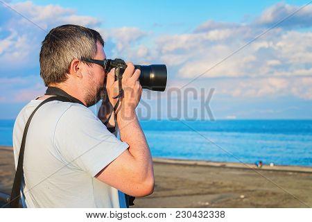 Man With Camera Taking Photos Of The Beach At The Mediterranean Sea At Santa Teresa Di Riva Near Mes