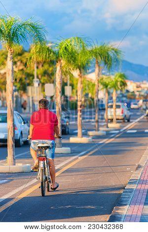 Man Riding A Bicycle In The Street At Santa Teresa Di Riva Near Messina, Sicily, Italy