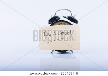 Note Paper Written Take A Break On Vintage Alarm Clock Over White Background