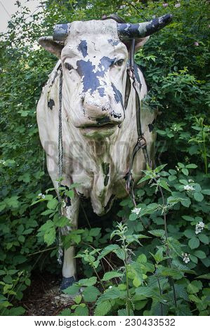 A Damaged White Cow Sculptures In Nature With Trees, Grass And Flower.