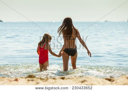 Little Girl Child And Mother Having Fun In Ocean. Kid And Woman Bathing In Sea Splashing Water. Summ