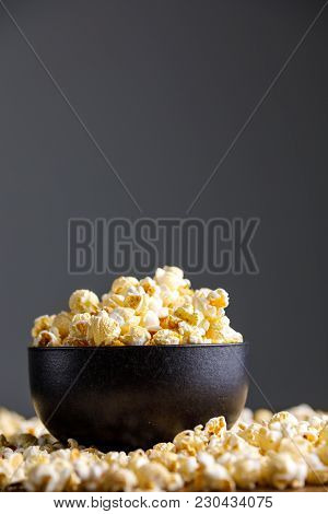 Popcorn In A Black Refined Ceramic Bowl And Around It.