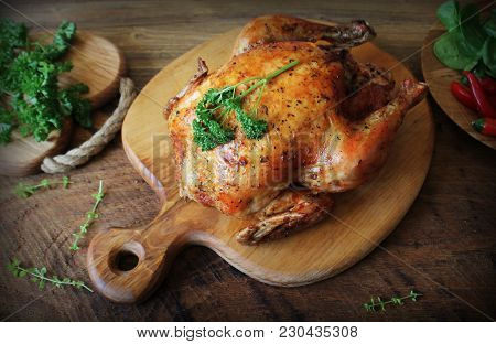 Whole Roasted Chicken With Herb On Cutting Board . Top View .