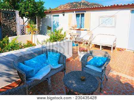 Cugnana, Italy - September 8, 2017: Courtyard Garden With Table And Chairs At The House On Costa Sme