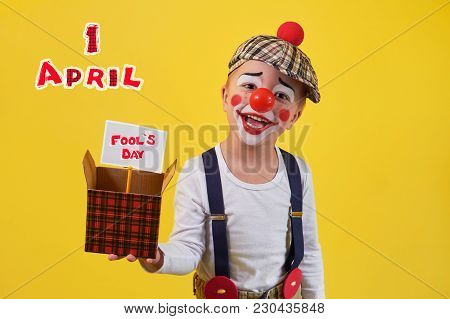 Beautiful Portrait Funny Kid In Celebration Costume Clown Isolated On Yellow Background. Child Clown