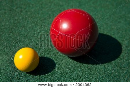 Closeup of a red bocce ball and a yellow palino poster
