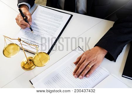 Lawyer Judge Reading And Writes The Document In Court At His Desk.