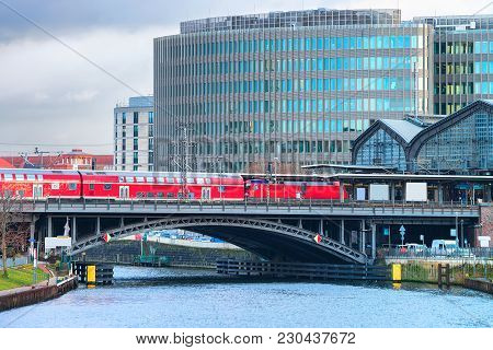 Business Downtown, Red Train And Bridge Over Spree River In Berlin Mitte, Germany