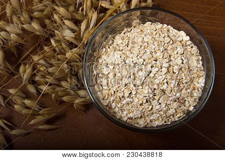 Oat Ears Stems And Oat Flakes In A Bowl On A Dark Brown Wood Background. Top View. Oat Flakes Small
