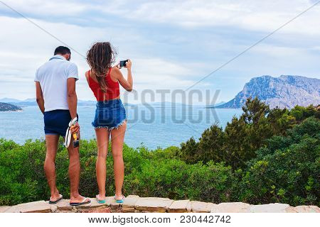 Couple Taking Photos Of Tavolaro Island At Capo Coda Covallo, San Teodoro In Olbia-tempio Province,