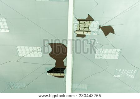 Close Up Of Holes In The Broken And Damaged Glass Windows On The Store Front After Riots