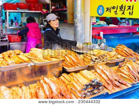 Busan, South Korea - March 12, 2016: Sellers Of Fried Fish In Street Fish Market In Jagalchi In Busa