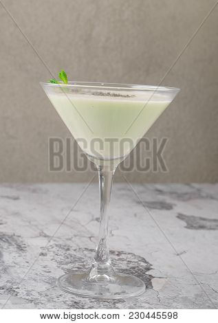 Top View Cream Milk Cocktail With Mint On A Gray Background. An Irish Cream Liquor In A Martini Glas