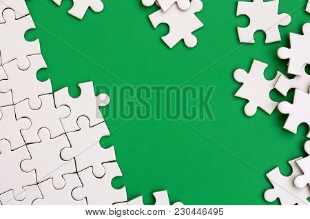 Fragment Of A Folded White Jigsaw Puzzle And A Pile Of Uncombed Puzzle Elements Against The Backgrou
