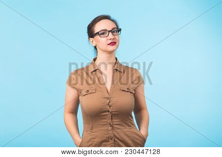 Elegant Cheerful Brunette In Eyeglasses Smiling At Camera On Blue Background.
