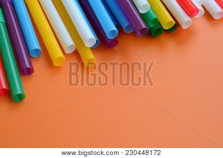 Many Colorful Straws For Drinks Lies On A Bright Orange Background Surface
