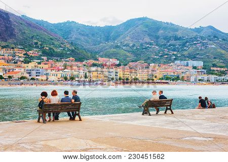 Cefalu, Italy - September 26, 2017: Seaside With People Sitting On The Benches In Cefalu Old Town, P