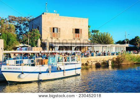 Marsala, Italy - September 19, 2017: Ship And People In Street Cafe At The Salt Evaporation Pond In