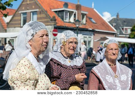 Urk, The Netherlands - September 02, 2017: Three Women With Traditional Clothing And Headgear At A L