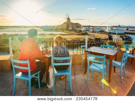 People In Street Restaurant At The Salt Evaporation Pond In Marsala, Sicily Island, Italy