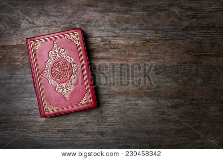 Holy book of Muslims on wooden background