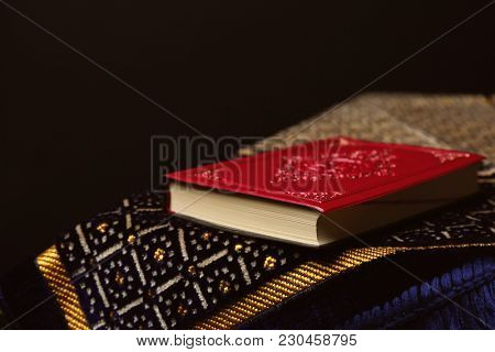 Holy book of Muslims and prayer rug against black background