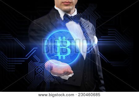 cryptocurrency, finance and business concept - close up of magician hand with virtual bitcoin symbol hologram over black background