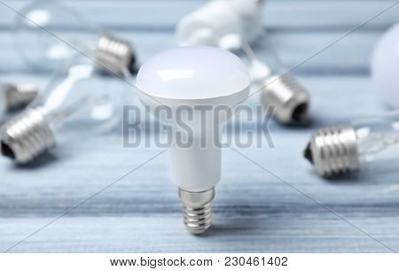 LED lamp and incandescent light bulbs on background