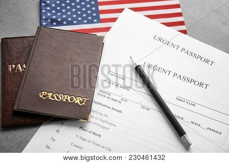 Passports, American flag and application forms on table. Immigration to USA