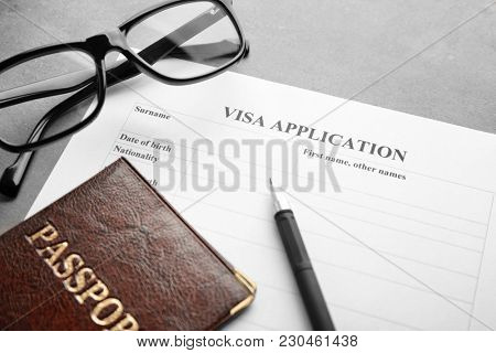 Passport, glasses and visa application form on table. Immigration reform