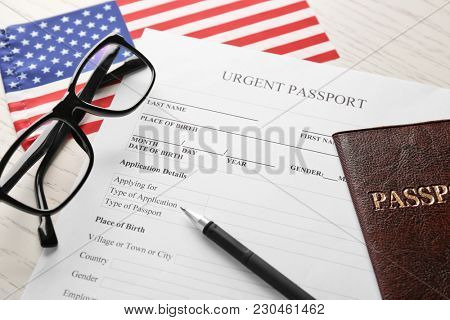 Passport, application form and American flag on table. Immigration to USA