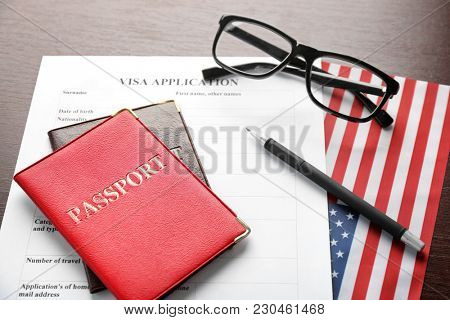 Passports, visa application form and American flag on table. Immigration to USA