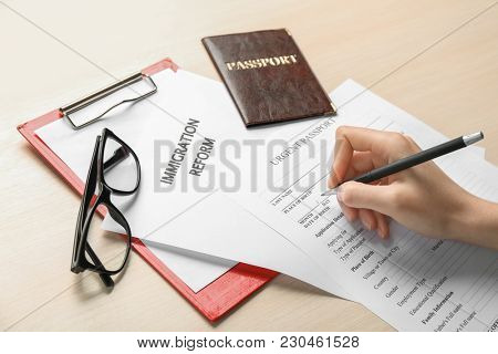 Woman filling urgent passport application form at table. Immigration and citizenship