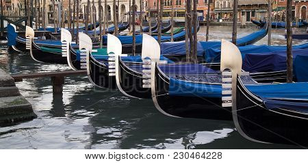 Moored Gondolas In A Row In Evening Light In Venice, Italy. Under The Main Blade There Is A Kind Of