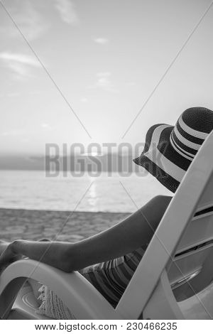 Lonely Woman Looking At Sunset As She Relaxes On A Recliner Chair On The Beach On Summer Vacation