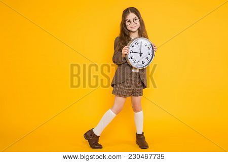 Portrait Of Adorable Long-haired Little Girl In Eyeglasses Wearing Brown Jacket, Shorts And White Kn