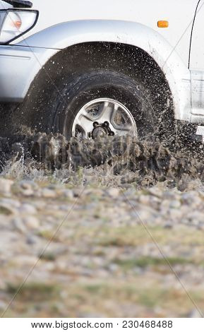 Car Wheel In A Spray Of Dirt And Water .