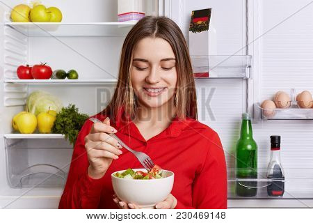 Horizontal Shot Of Cheerful Female Holds Bowl With Fresh Vegetable Salad, Stands Near Friedge Full O