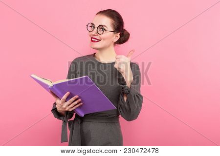 Portrait Of Attractive Cheerful Businesswoman With Hair Bun In Formal Dress And Eyeglasses Reading I