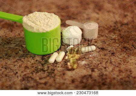 Whey Protein Powder In Scoop With Vitamins. Athletes Require Multiple Supplements To Remain Healthy.